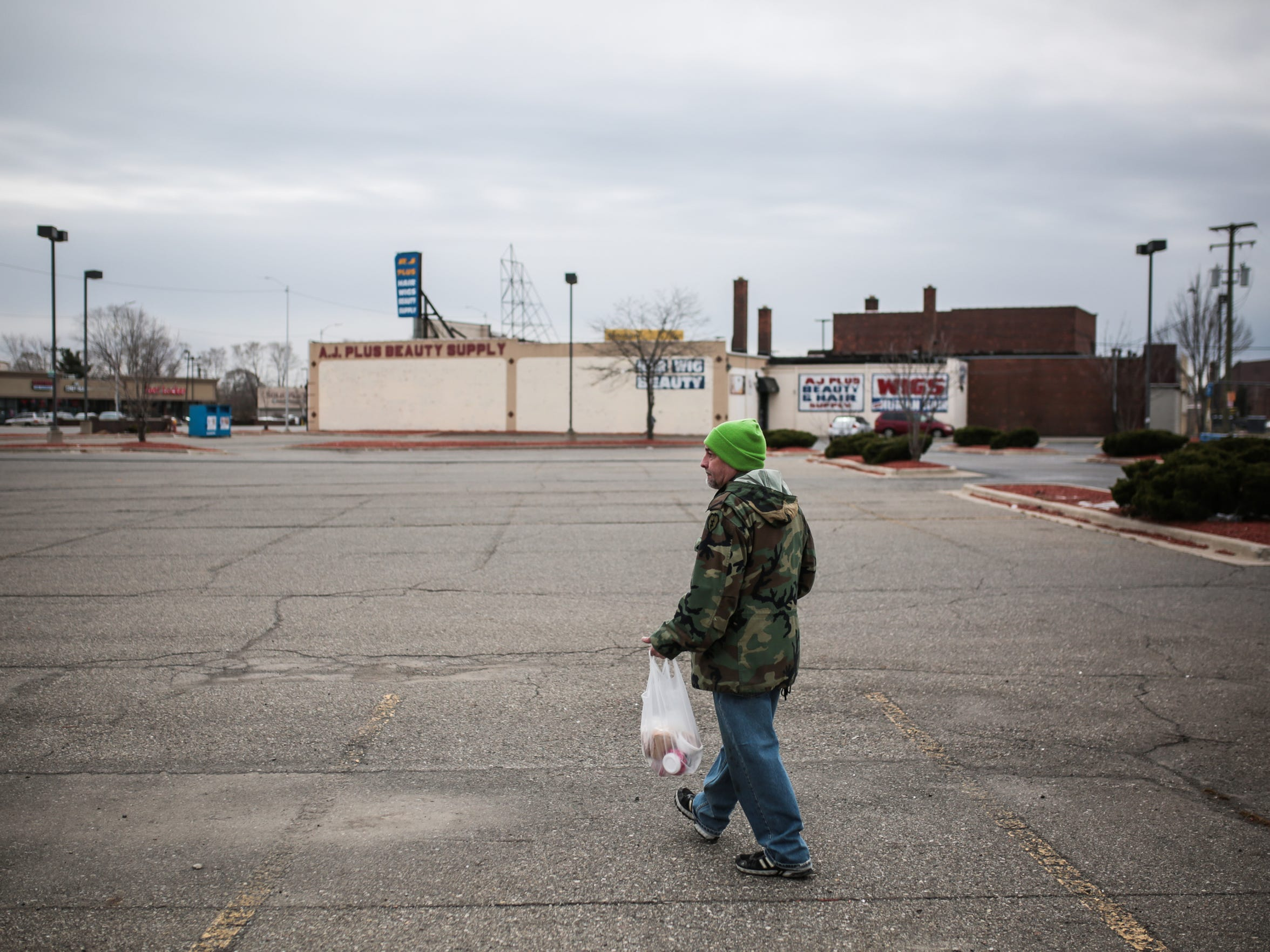 "Michael Terrell, 58, of Detroit, walks home after getting a meal from the Salvation Army's Bed and Bread program food truck on March 9, 2017, on Detroit's east side. ""I was homeless for three years,"" Terrell said. ""That's why I took the first place that came along."""