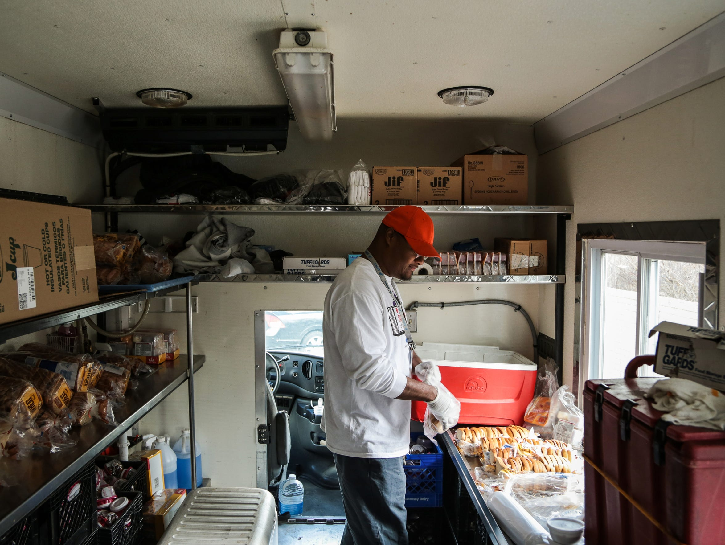 Lannell Smith, 43, of Detroit prepares sandwiches on