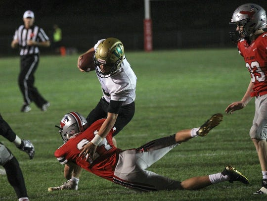West High quarterback Evan Flitz gets tackled as he