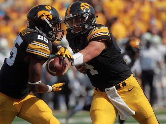 Iowa quarterback Nate Stanley hands the ball to running back Akrum Wadley during the Hawkeyes' game against North Texas at Kinnick Stadium on Saturday, Sept. 16, 2017.