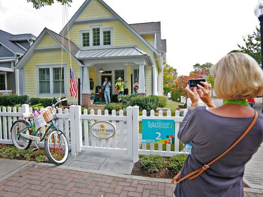 A woman takes a photo of one of bands performing at the Fourth Annual Carmel Porchfest, Sunday, September 17, 2017.   41 performances were held on 20 porches in the Carmel Arts & Design District.