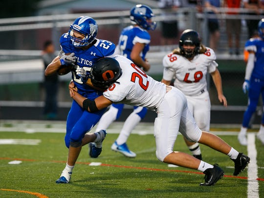 McNary's Lucas Garvey (23) is tackled by Sprague's Teagan Quitoriano (20) on Friday, Sept. 15, 2017, at McNary High School in Keizer, Ore. Sprague defeated McNary 62-6.