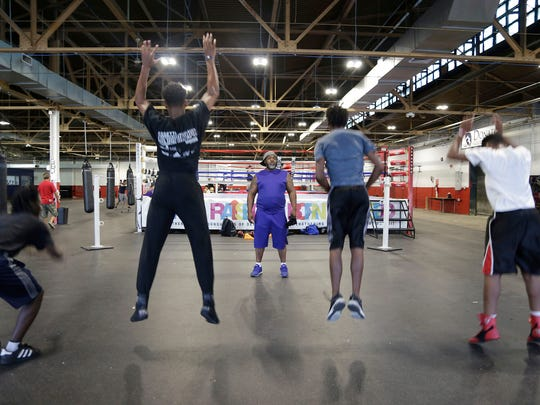Coach Tony Perry monitors calisthenics as students take part in the after school programs that include tutoring and exercise at the Downtown Boxing Gym in Detroit on Friday, Sept. 22, 2017.