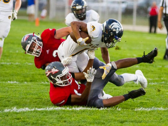 Fraser's Joshua Brady is brought down by Reid Kerr (2) and Trey Green (14) from Port Huron High School during their game Sept. 22.