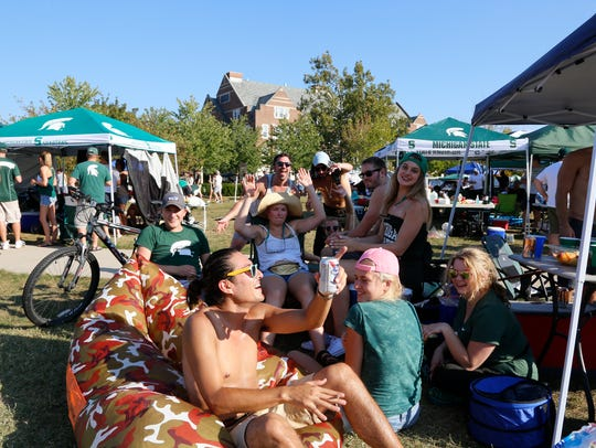 Football fans tailgate before a Michigan State University