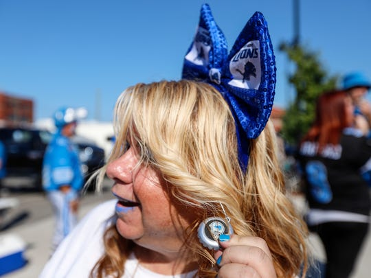 Lions fan Tracy Sekula of Sterling Heights, shows off the Detroit Lions earrings that she made during tailgate at the Eastern Market.