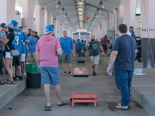 Left to right, Sam Falk of Tecumseh, Josh Maxam of Ypsilanti, Brandon Smith of Tecumseh and Rob Wilson of Fenton play corn hole during tailgate at the Eastern Market.