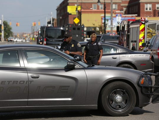 Detroit Police officers work at a scene where a person
