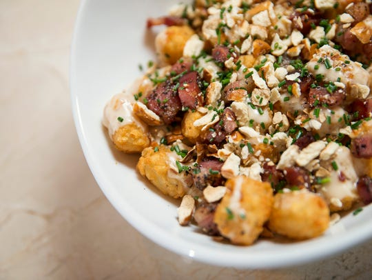Beer cheese covered tater tots are topped with bacon,