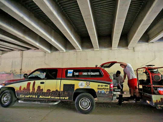 Romello Maxwell, left, and James Thompson, with the Indianapolis Graffiti Abatement Unit, gather supplies to start a job painting over graffiti at an overpass along Fall Creek on the Fall Creek Greenway, Tuesday, Sept. 26, 2017.