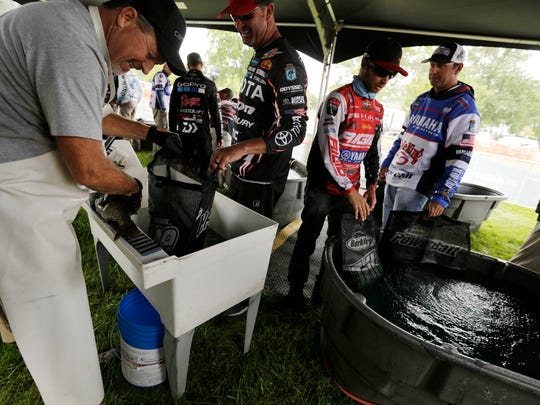 Bill Myers, left checks fish caught before weigh in during the Bassmaster Elite Series Tournament at Lake St. Clair Metropark in Harrison Township on Thursday, August 24, 2017.