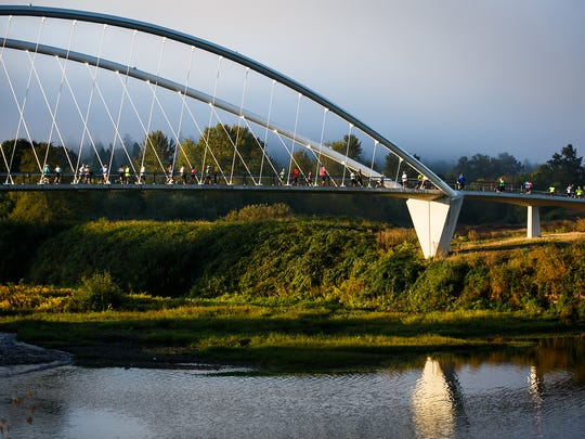 Athletes cross the Peter Courtney Minto Island Footbridge  at the start of the Rotary Triathlon of Salem on Sunday, Oct. 1, 2017. After the swimming portion was cancelled, the event became a duathlon, starting with a one mile run, then an Olympic or sprint distance cycling race, followed by a 5k or 10k run.