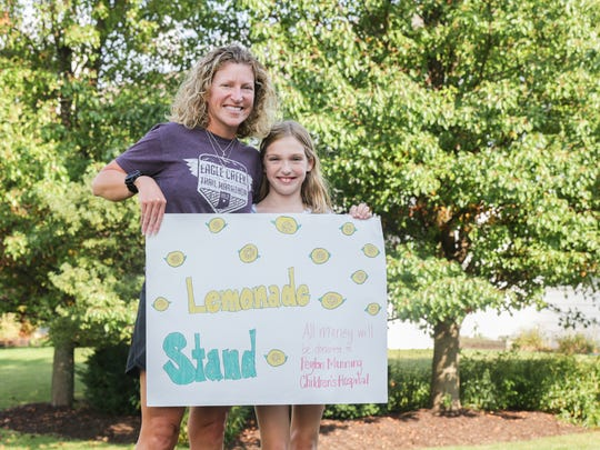 Julie, left, and Gwyneth Gebhart hold a sign used by