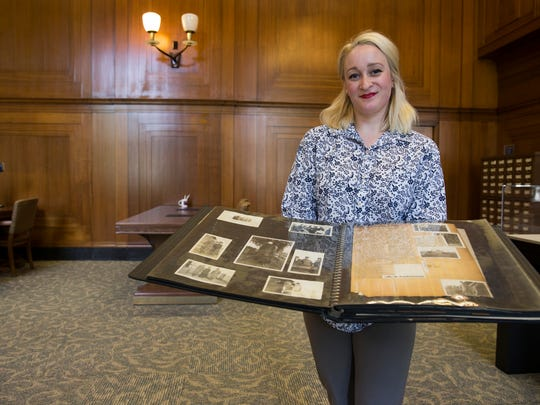Lauren Patton holds a World War I era scrapbook of