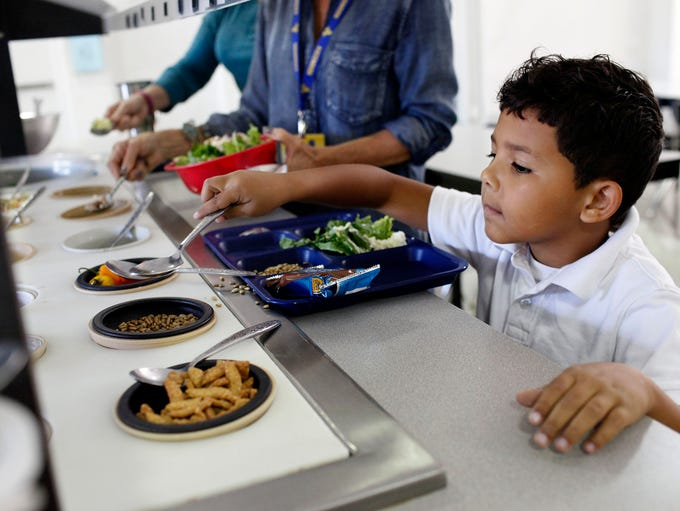 Student Kyron Dickerson, 7, selects items from the
