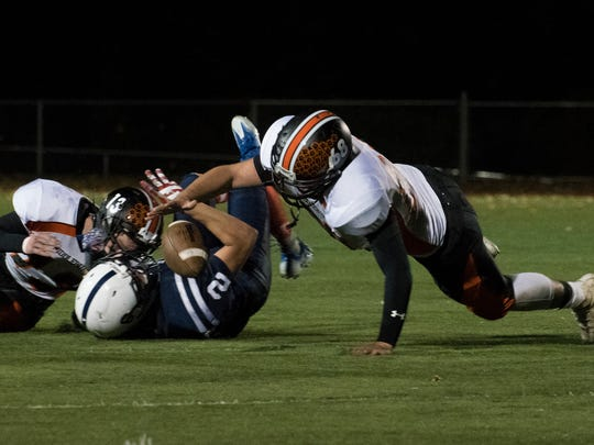 Middlebury's Camden Devlin (68) battles for the fumble with Burlington's Kevin Garrison (2) during the high school football game between the Middlebury Tigers and the Seahorses at Buck Hard field on Friday night.