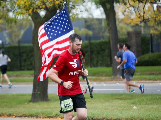 David Mahon, 33, of Grosse Pointe runs the marathon with an American flag, during the 40th Annual Detroit Free Press/Chemical Bank Marathon in Detroit on Sunday, Oct. 15, 2017.