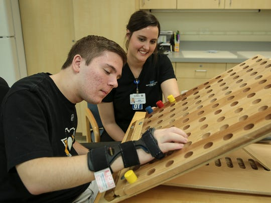 Anthony Mastronardi of Macomb Township, left, works at a pegboard as his occupational therapist Brittany Falzon encourages him during an occupational therapy session, Wednesday, May 17, 2017 at DMC's Rehabilitation Institute of Michigan in Detroit.