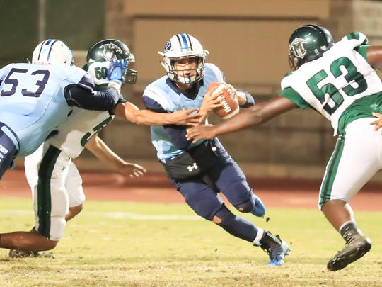 Redwood's QB Hector Gonzalez (10) attemps to avoid