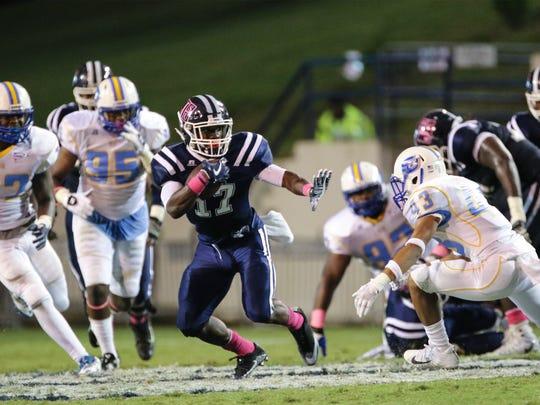 Jackson State tailback Jordan Johnson runs away from Southern defenders at Memorial Stadium Saturday night.