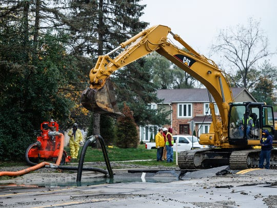 Workers examine the broken water main on West 14 Mile Road between Drake and Farmington roads in West Bloomfield Township, Tuesday, October 24, 2017.