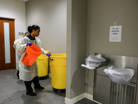 Providence Park Hospital housekeeping members Marquitta Odell and Lisa Emery gather buckets of water to flush toilets at Providence Park Hospital in Novi on Tuesday Oct. 24, 2017, after a boil advisory was issued.