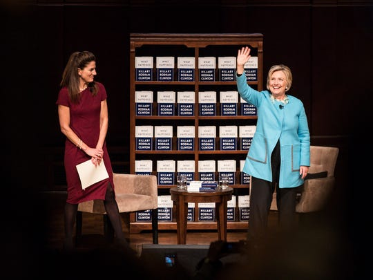 Hillary Clinton waves at the audience after a Q&A session with U-M professor Anne Curzan, left, at the Hill Auditorium on the U-M campus in Ann Arbor on Tuesday, October 24, 2017.