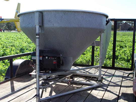 The hopper for aerial seeding is filled with seed and the flow rate can be controlled by the helicopter pilot. The hopper can hold 300-400 pounds of seed.