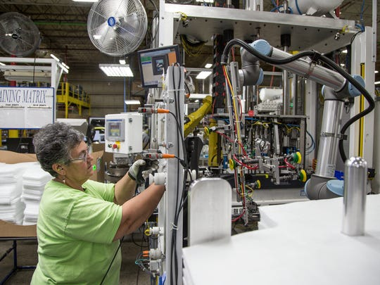 Phyllis Aslinger inspects a Chevrolet Cruz door assembled by collaborative robots at the IAC plant in Huron, Ohio, on Thursday, October 19, 2017.