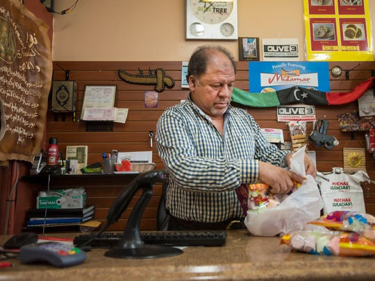 Shop owner Taher Misurati bags up a customer's groceries, Friday, Oct. 20, 2017, at the Olive Tree Market on South College Avenue in Fort Collins, Colo.