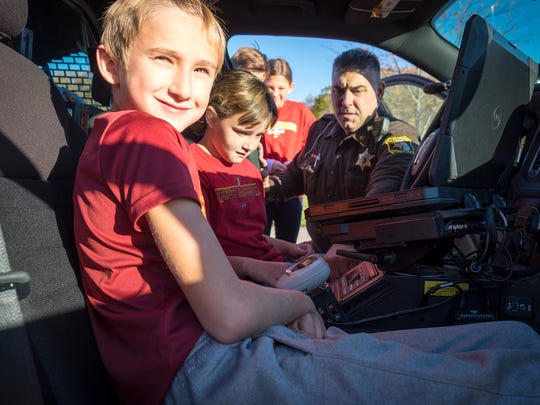 Indian Woods fifth-grader Nick Gorinac, 10, left, smiles while St. Clair County Deputy Damon Duva shows Riley Thompson, 10, the different buttons on the console of his police cruiser Oct. 26.The Indian Woods Student Council raised money to buy fleece and made blankets that are being donated to the St. Clair County Sheriff's Department to give to children in emergencies.