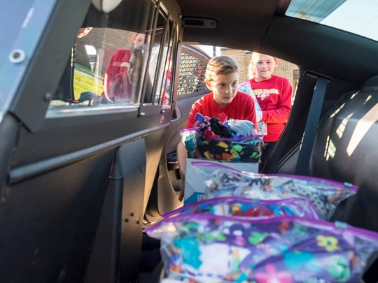 Indian Woods Elementary School fifth-grader Kenny Thomas, 10, loads fleece blankets into the back of a St. Clair County Sheriff's police cruiser Oct. 26. The Indian Woods Student Council raised money to buy fleece and made blankets that are being donated to the St. Clair County Sheriff's Department to give to children in emergencies.