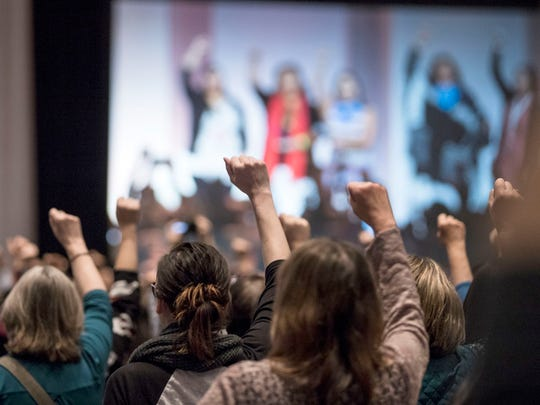 Attendees raise their fists as they hear the opening prayers song offered by five indigenous women during the Women's Convention at Cobo Center in downtown Detroit, Friday, October 27, 2017.