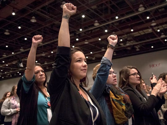 Bethany Bradley, center, raises her fist as they listen