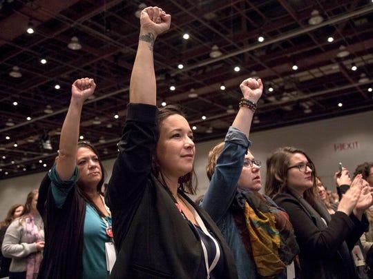 Bethany Bradley, center, raises her fist as they listen