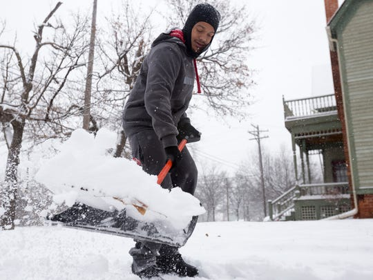 Archie Tharrett, 30, shovels snow for his grandmother, aunt, and a couple of neighbors on Sunday, Dec. 11, 2016 in the Woodbridge neighborhood in Detroit.