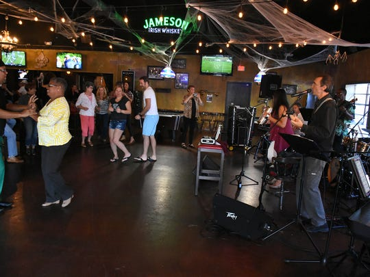 Patrons dance to the Latin tunes of West Side Tropico. Four bands came together in a benefit performance for hurricane relief at Music for Neighbors, October 29 at Whiskey Park restaurant.