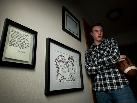 Fort Collins High School sophomore quarterback Hayden Iverson poses in the hallway outside his bedroom, next to a caricature drawing of himself and his late mother and a quote written down by his mother, Wednesday, Nov. 1, 2017 at his home in Fort Collins, Colo.