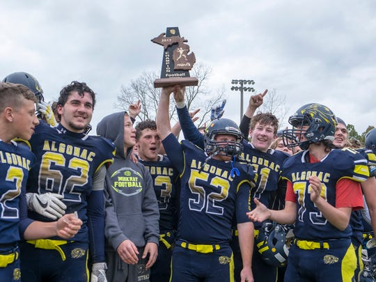 The Algonac High School Muskrat football team cheers as defensive tackle Donovan Huber (52) holds up the MHSAA Division 5 trophy after defeating Ida High School 24-16 during the MHSAA Division 5 championship game Nov. 4.