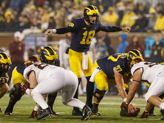 Michigan quarterback Brandon Peters (18) talks to teammates
