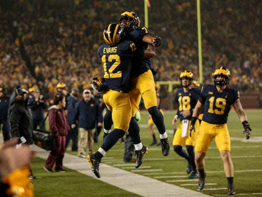 Michigan running back Chris Evans (12) celebrates his