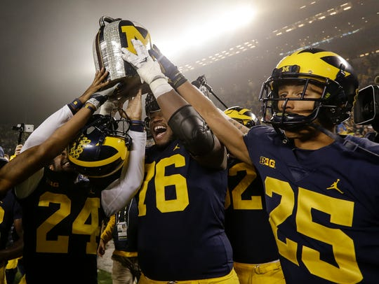 Michigan's offensive lineman Juwann Bushell-Beatty (76) raises the Little Brown Jug to celebrate the 33-10 victory over Minnesota on Nov. 4.