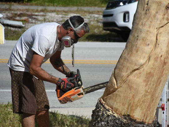 Sculptor Elvis Caron works on the base of the piece. Hackman commissioned a sculpture of a mermaid carved from the trunk of a Norfolk pine that he cut down in anticipation of Hurricane Irma.