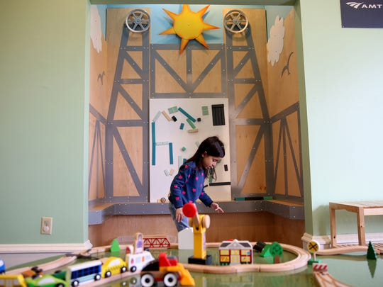 May Lucas, 5, of Keizer, plays near a model of the