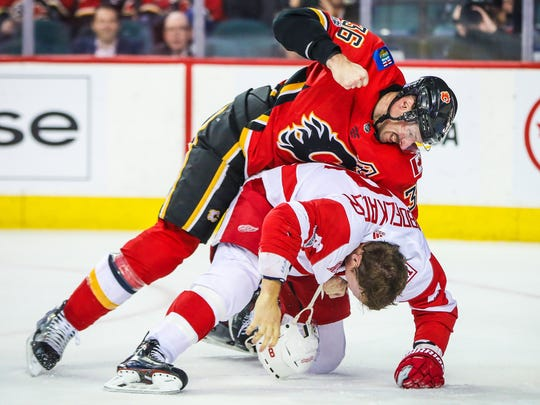 Flames right wing Troy Brouwer (36) and Red Wings left wing Justin Abdelkader (8) fight during the second period of the Wings' 6-3 loss on Thursday, Nov. 9, 2017, in Calgary, Alberta.