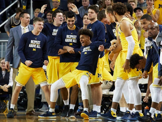 Michigan bench reacts to a basket during the second