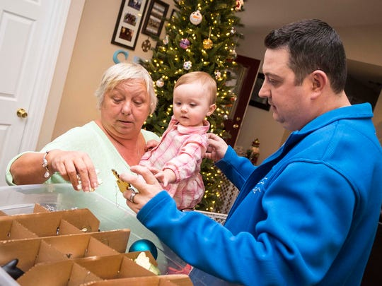 Blake Stringer, right, and his mother-in-law Nancy Wehner, left, of Mesa, Arizona, sort through Christmas decorations with Blake's daughter, Blakelynn, Wednesday, Nov. 15, 2017. Wehner is one of the many family members who came into town to help Blake and his wife, Jennifer Stringer, after she donated a kidney to him in October.