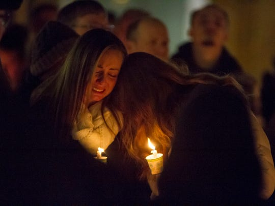 Kimberly Lennoo, right, cries on Christa Pilarowski's shoulder during a candlelight vigil for Cheryl Myny Thursday, Nov. 16, 2017. Myny was shot and killed by her husband Saturday inside her business, Jump N Jam, where Lennoo and Pilarowski both work.