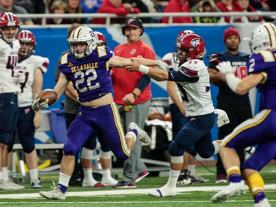 Warren De La Salle running back Evan Vaillancourt (22) is chased by Livonia Franklin linebacker Marino Diponio  (33) during the first half of the MHSAA Division 2 championship game at the Ford Field in Detroit, Friday, November 24, 2017.