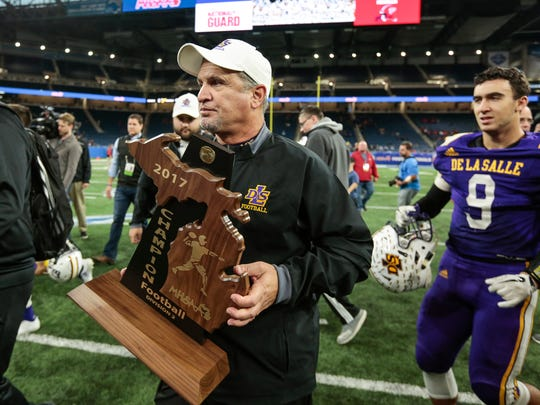 Warren De La Salle head coach Mike Giannone holds an MHSAA Division 2 championship trophy after defeating Livonia Franklin 42-6 at the Ford Field in Detroit, Friday, November 24, 2017.